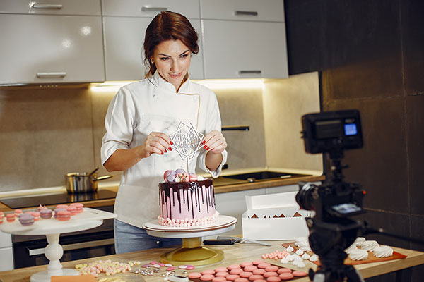 Woman teaching in front a camera how to decorate a cake