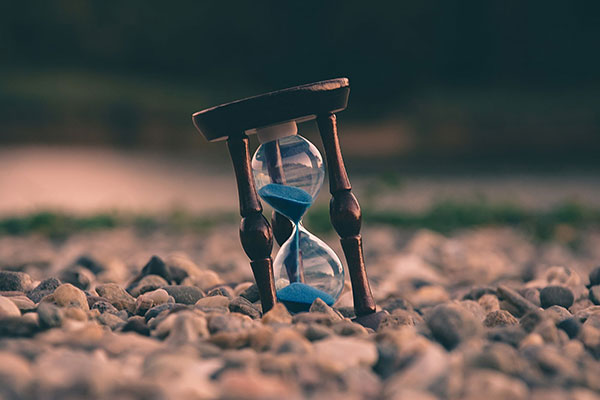 An sand hour glass clock on the ground