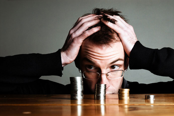 confused man looking at money