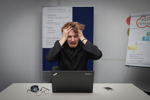 Frustrated man at laptop