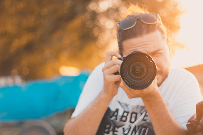 man taking photograph with a DSLR camera