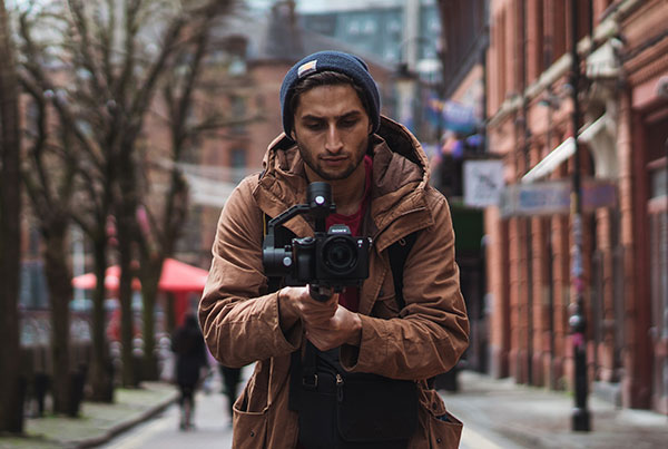videographer walking on the street while filming with camera