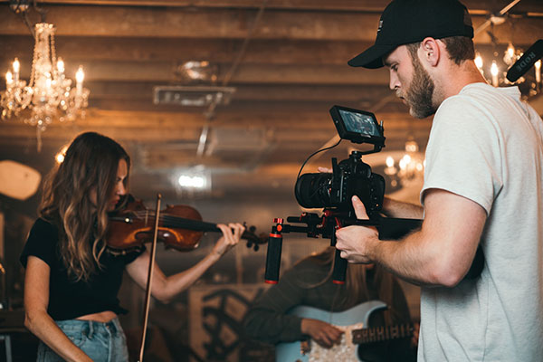 Woman teaching how to play violin while being filmed by a friend