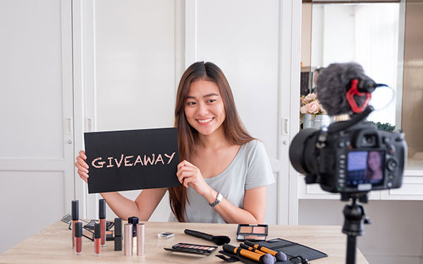 a girl holding a giveaway sign in front of a camera
