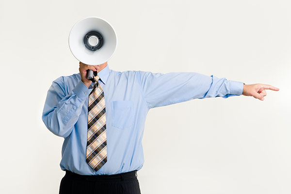 a man holding a megaphone pointing at a direction to promote something