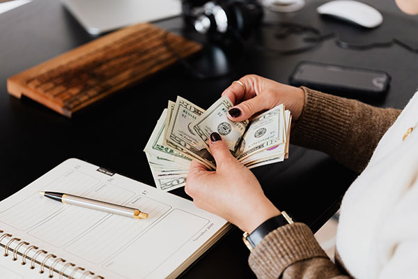 a woman counting dollar bills and determining business budget