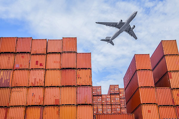 an airplane flying over shipment containers