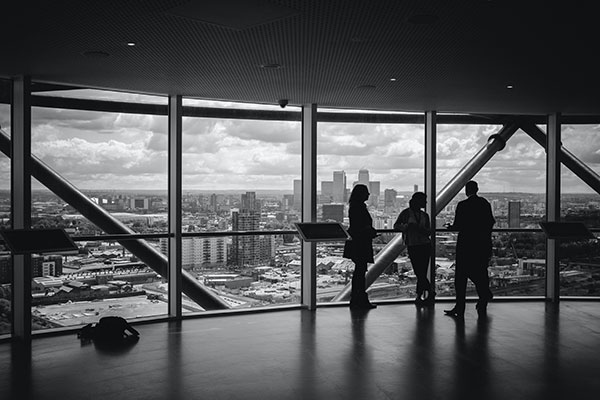 three people talking about business while standing