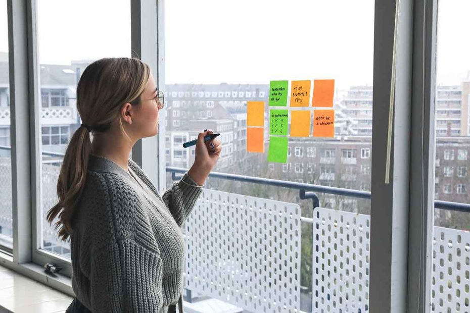 a woman writing business ideas on sticky notes