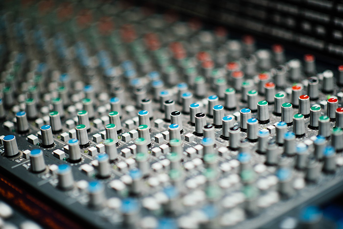 Lots of nobs and switches on a mixing panel